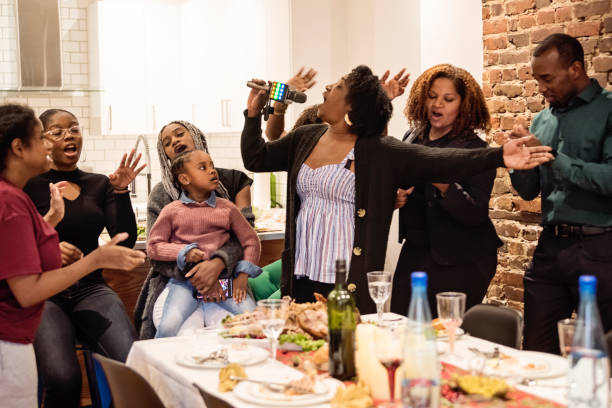 Multi-generation family singing at Thanksgiving dinner. Family time for Thanksgiving dinner. Multi-generation members of african-american having fun singing and dancing with karaoke microphone. Modern appartement with brick wall. Horizontal indoors waist up shot with some copy space. haitian ethnicity stock pictures, royalty-free photos & images