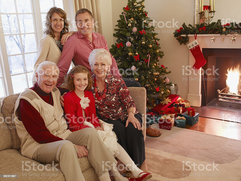Multi-generation family sitting on sofa near Christmas tree royalty-free stock photo