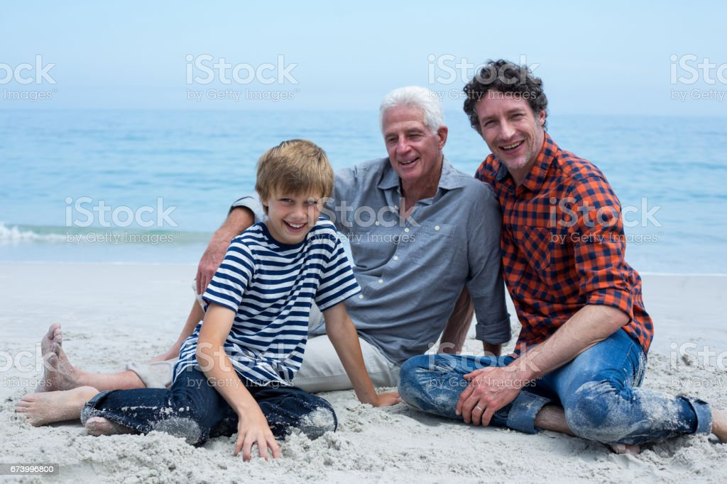 Multi-generation family smiling while relaxing at sea shore royalty-free stock photo