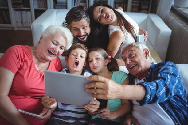 familia de múltiples generaciones teniendo un selfie en tableta digital en sala de estar - memorial day fotografías e imágenes de stock