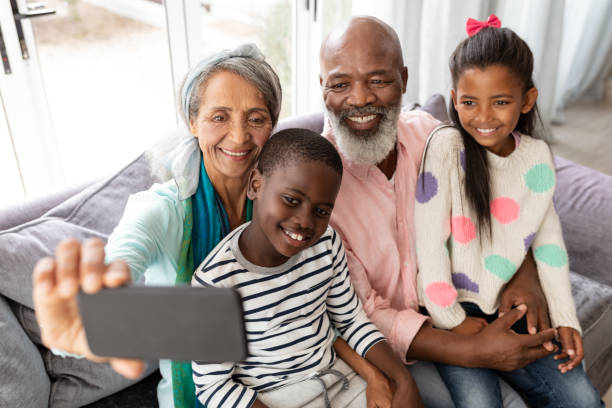 Multi-generation family taking selfie with mobile phone on a sofa in living room stock photo