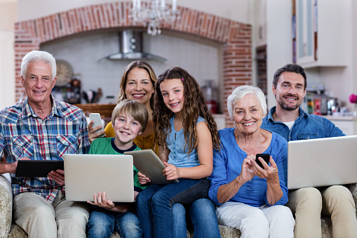 istock Multi-generation family using a laptop, tablet and phone 663137178