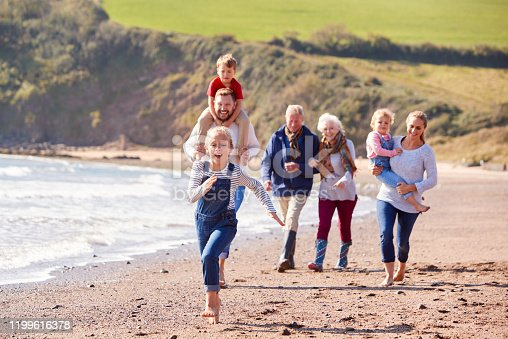 istock Multi-Generation Family Walking Along Shoreline Of Beach By Waves Together 1199616378