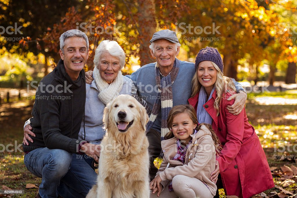 Multi-generation family with dog at park stock photo