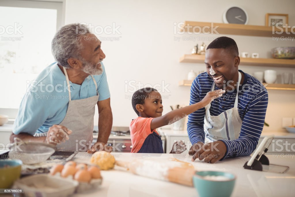 Multi-generation family with flour on the nose standing in the kitchen stock photo
