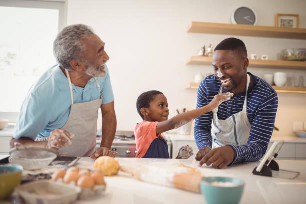mehr-generationen-familie mit mehl auf der nase stehen in der küche - seniorenwohnungen stock-fotos und bilder