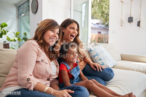 Multi-Generation Female Hispanic Family On Sofa At Home Watching TV Together