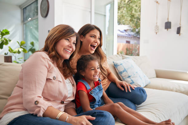 Multi-Generation Female Hispanic Family On Sofa At Home Watching TV Together stock photo