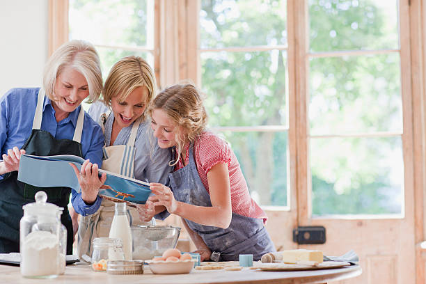 multi-generation females looking at cookbook and baking in kitchen - woman home magazine stockfoto's en -beelden