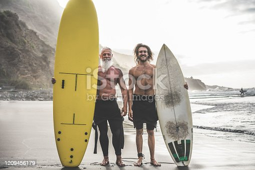 Multigeneration friends going to surf on tropical beach - Family people having fun doing extreme sport - Joyful elderly and healthy lifestyle concept