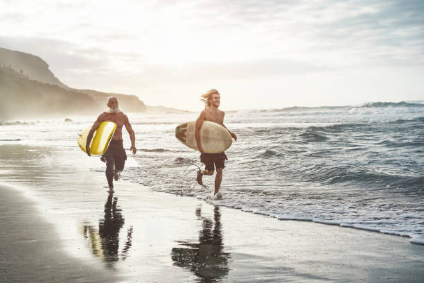 Multigeneration friends going to surf on tropical beach - Family people having fun doing extreme sport - Joyful elderly and healthy lifestyle concept - Main focus on young guy stock photo