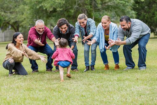 Multi-generation Hispanic family, baby walking toward