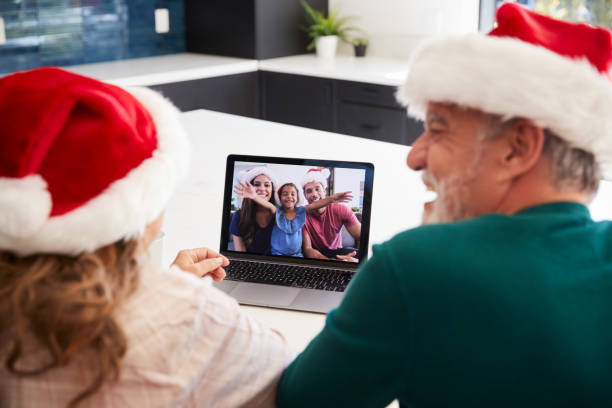 Multi-Generation Hispanic Family Wearing Santa Hats With Laptop Having Video Chat At Christmas stock photo
