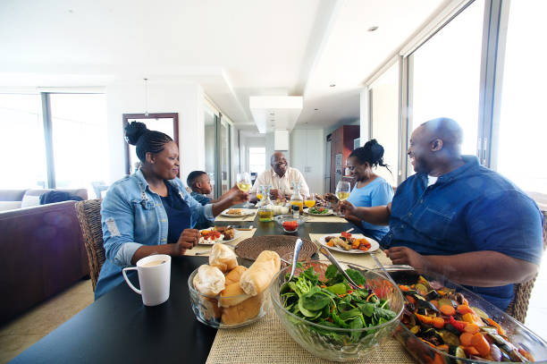 Multi-generational African family cheers at the lunch table stock photo