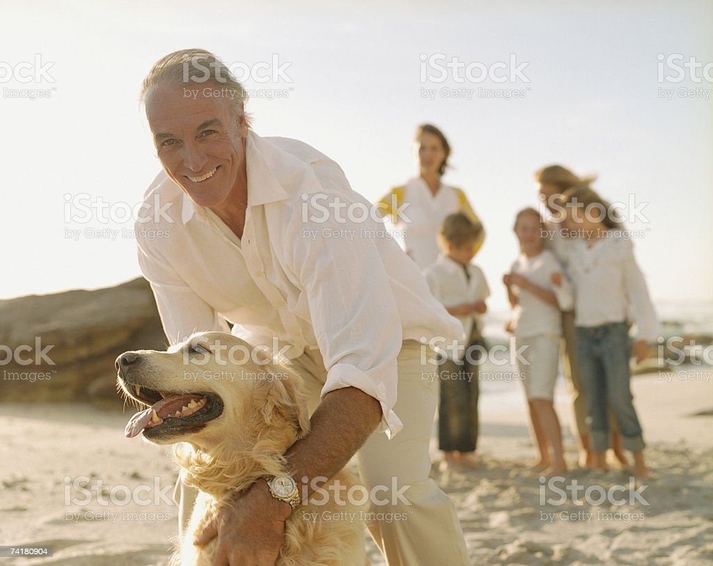 Multigenerational family at beach with dog stock photo