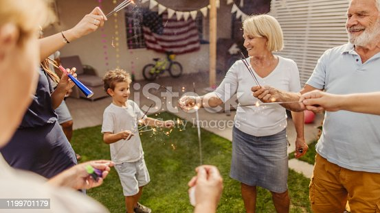 Photo of a multigenerational family celebrating Fourth of July in their yard