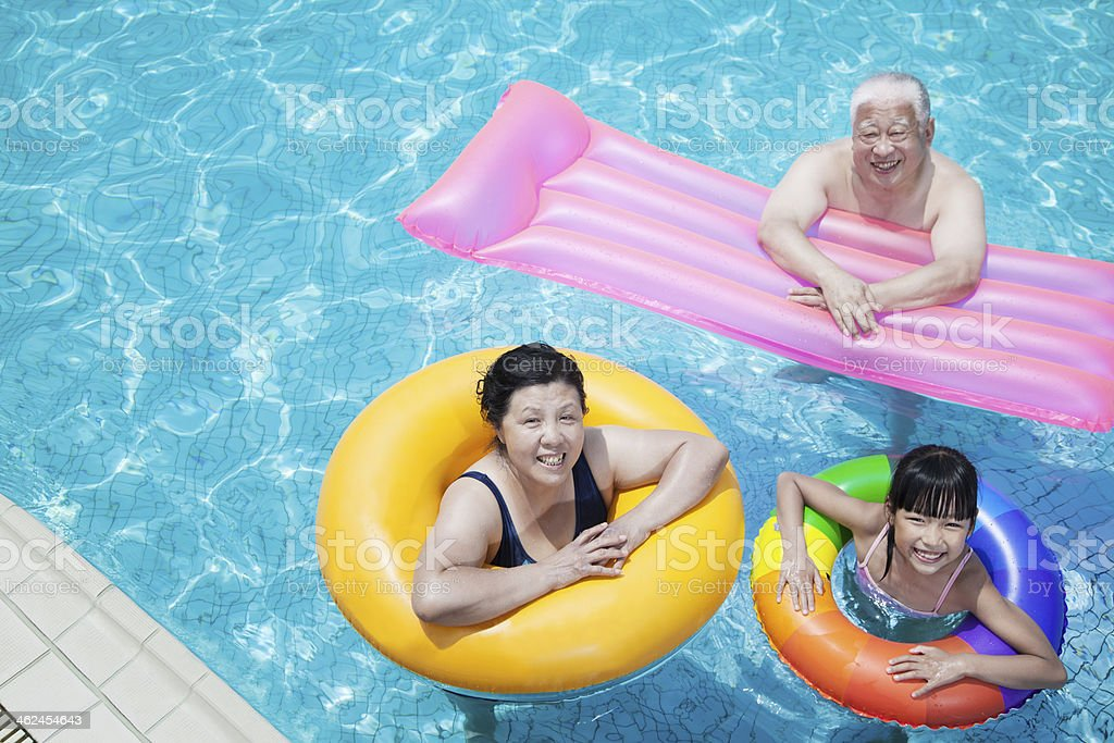 Multi-generational family playing in the pool with inflatable tubes stock photo