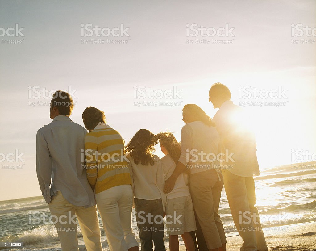 Multigenerational family portrait outdoors at sunset stock photo