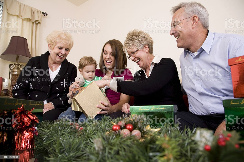 Multi-Generational Family Smiling While Opening Christmas Presents royalty-free stock photo