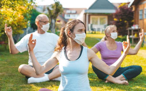 Multigenerational group of people making yoga exercises outdoors wearing medical protective masks Concept of life during or after quarantine, coronavirus protection measures yoga instructor stock pictures, royalty-free photos & images