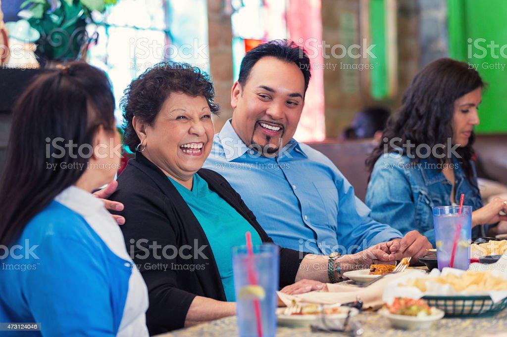Multi-Generational Hispnic family enjoying meal in restaurant stock photo