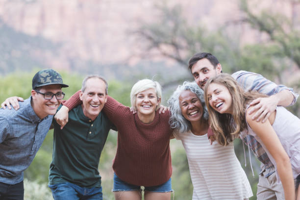Multi-generational of friends posing together outside stock photo