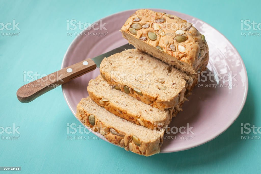 Multi-Grain Bread slice with knife on ceramic plate stock photo