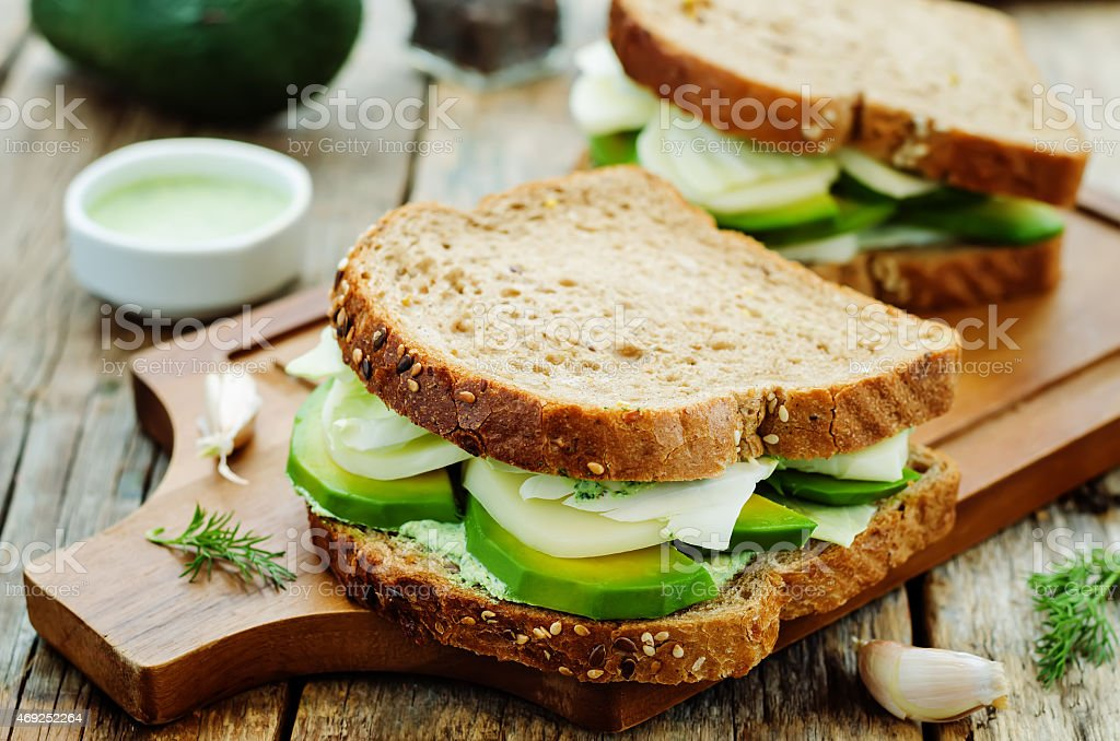 Multigrain bread with avocado, cheese, cabbage and herbs stock photo