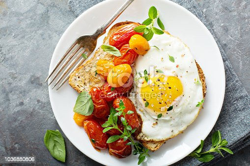 Multigrain toast with fried egg, fresh herbs and roasted tomatoes