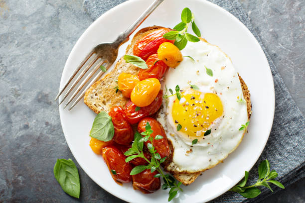 Multigrain toast with fried egg and roasted tomatoes stock photo