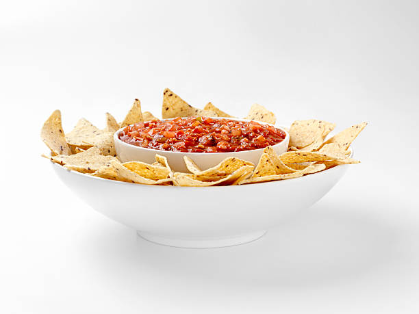 Multigrain Tortillia Chips with Chunky Salsa Multigrain Tortillia Chips with Chunky Salsa. With Natural drop shadow and gradated background -Photographed on Hasselblad H3D2-39mb Camera salsa sauce stock pictures, royalty-free photos & images