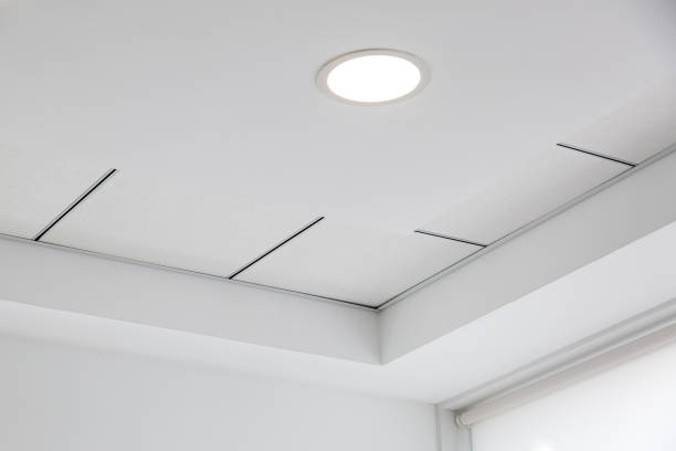 multi-level ceiling with three-dimensional protrusions and a suspended tiled ceiling with a built-in round led light. - led painel imagens e fotografias de stock