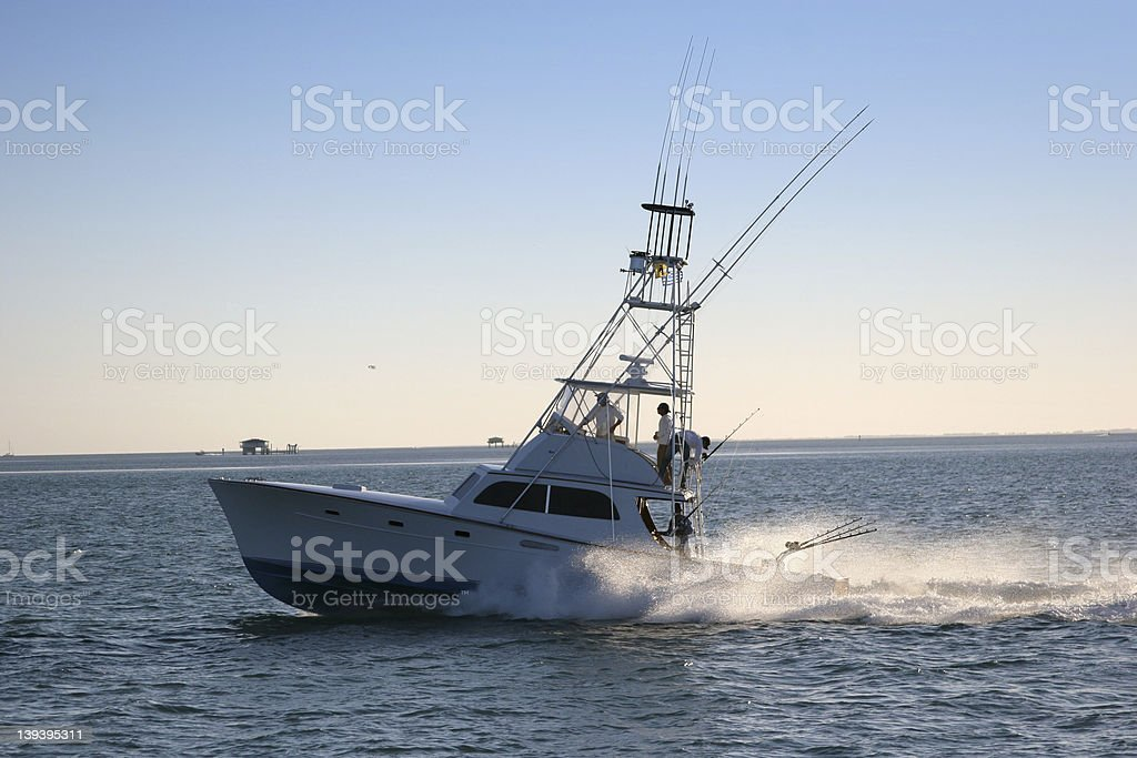 Multi-Level fishing boat on the water with fishing poles stock photo