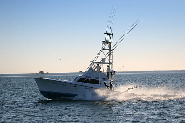 multi-level fishing boat on the water with fishing poles - fishing boat stock pictures, royalty-free photos & images