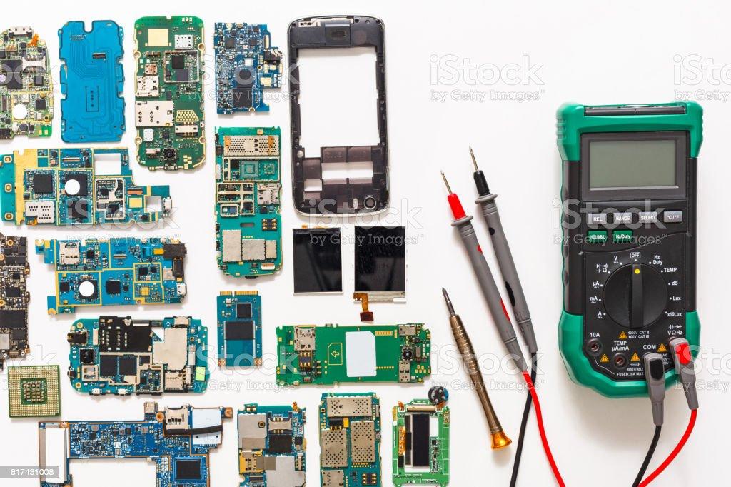 Multimeter and broken mobile electronics at repair shop stock photo