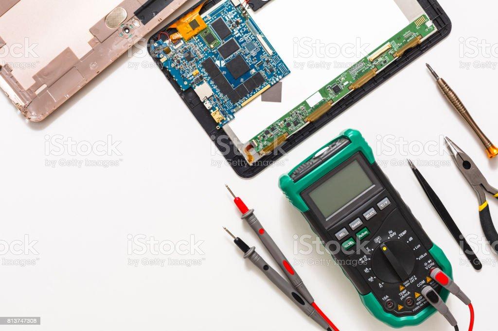 Multimeter and broken tablet, electronics at repair shop stock photo