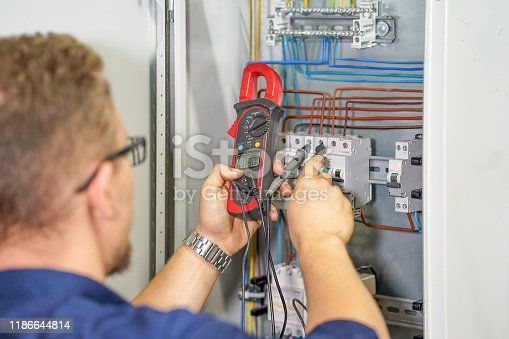 istock Multimeter is in hands of electrician on background of electrica 1186644814