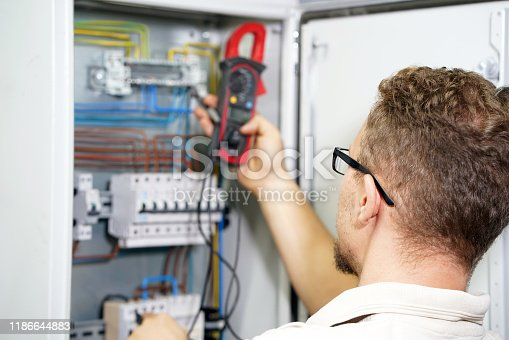 istock Multimeter is in hands of electrician on background of electrica 1186644883
