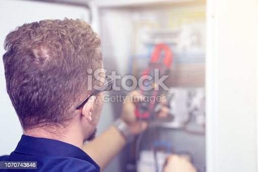 istock Multimeter is in hands of electrician on background of electrical automation cabinet. 1070743646