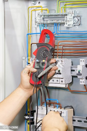istock Multimeter is in hands of electrician on background of electrical automation cabinet. 1070743686