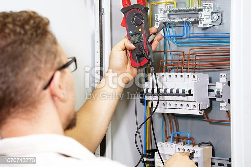 istock Multimeter is in hands of electrician on background of electrical automation cabinet. 1070743770