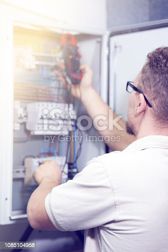 istock Multimeter is in hands of electrician on background of electrical automation cabinet. Adjustment of electrical control circuit for industrial equipment. 1085104958