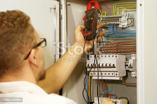 istock Multimeter is in hands of electrician on background of electrical automation cabinet. Adjustment of electrical control circuit for industrial equipment. 1085104964