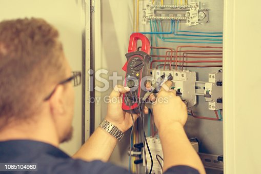 istock Multimeter is in hands of electrician on background of electrical automation cabinet. Adjustment of electrical control circuit for industrial equipment. 1085104980