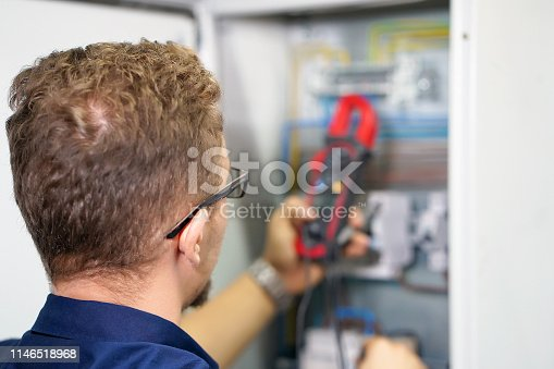 istock Multimeter is in hands of electrician on background of electrical automation cabinet. Adjustment of electrical control circuit for industrial equipment. 1146518968