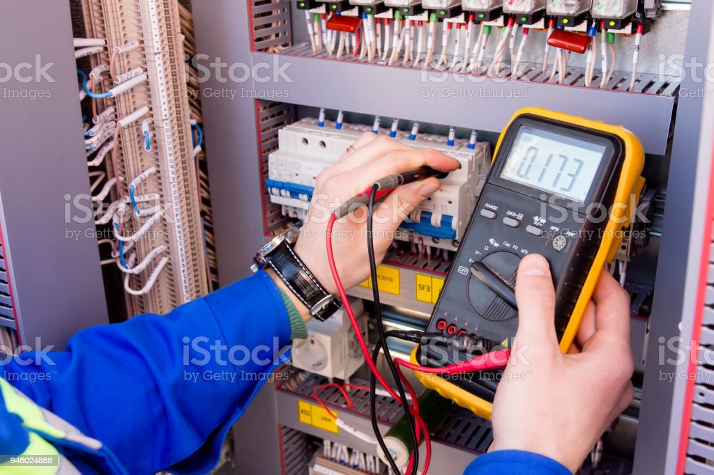 multimeter is in hands of engineer in electrical cabinet. Adjustment of automated control system for industrial equipment control cabinets. electrician measures voltage by tester. - Zbiór zdjęć royalty-free (Bezpieczeństwo)