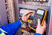 multimeter is in hands of engineer in electrical cabinet. Adjustment of automated control system for industrial equipment control cabinets. electrician measures voltage by tester