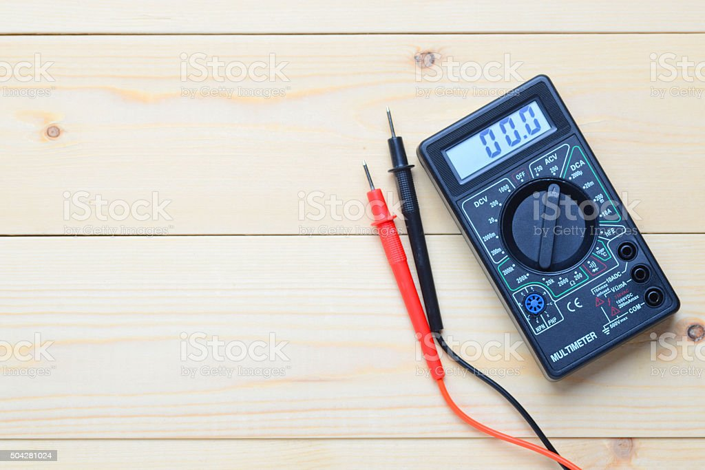 multimeter lies on a wooden board stock photo