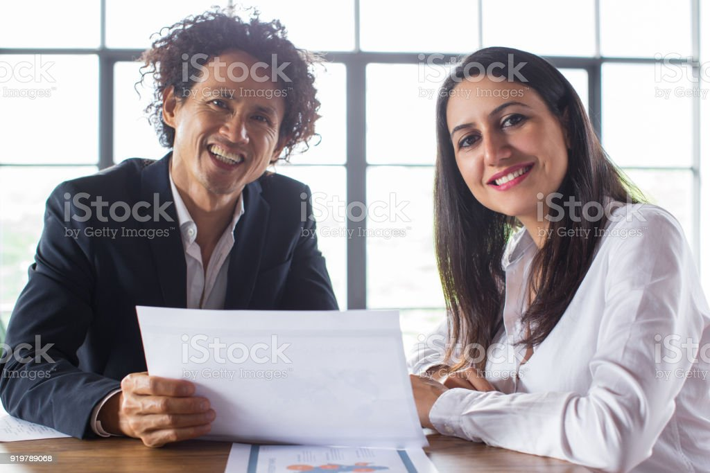 Multi-national colleagues smiling at camera stock photo