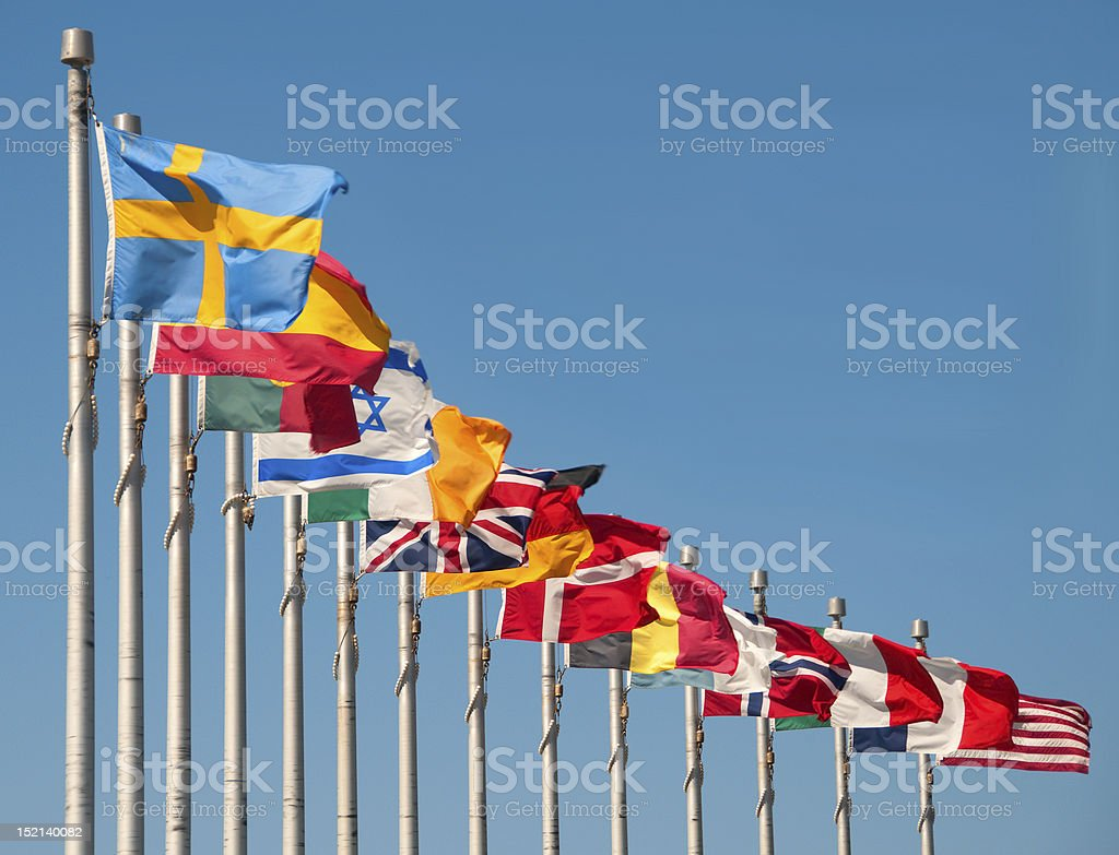 Multinational flags flying against blue sky stock photo
